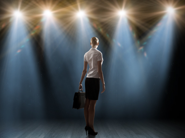 Woman on stage in spotlight for VOT Virtual Assistant Understudy Program remote short term easy projects from home